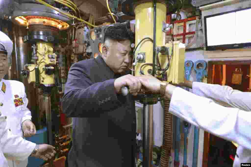 Кім Чен Ин дивиться в перископ на субмарині під час інспекції одного з місць дислокації північнокорейських ВМС. Червень 2014 року