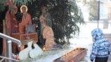 Иса пайғамбардың дүниеге келуін бейнелейтін композицияға қарап тұрған бала. Алматы, 7 қаңтар 2014 жыл.
