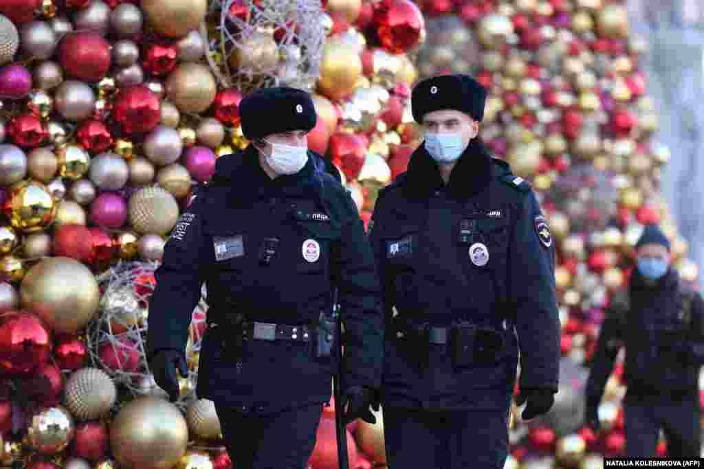 Руски полицаи с предпазни маски патрулират около празничната украса за новогодишните и коледни празници.