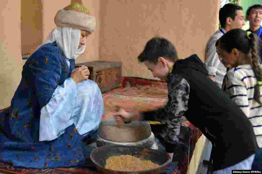 Программа «Ночи музеев - 2018» в Музее Алматы состояла из 12 пунктов. В их числе экспозиция «Живой музей». Например, эта женщина в зале Средних веков демонстрирует процесс переработки зерна. Детворе захотелось попробовать своими руками.