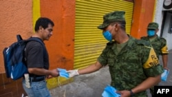Mexican soldiers distribute face masks as prevention against the swine-flu virus in Mexico City.
