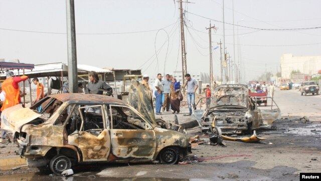 Residents gather at the site of a bomb attack in Basra on May 20.