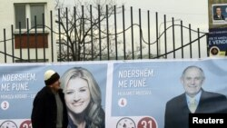 Kosovo -- An ethnic Albanian passes by an election poster in the capital Pristina, 09Dec2010