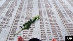 A Muslim woman prays at the Potocari memorial cemetery, near Srebrenica, in March 2010.