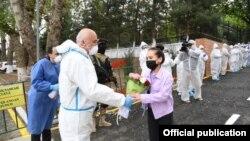 Министр здравоохранения Узбекистана Алишер Шадманов вручает букет цветов пациентке, полностью выздоровевшей от коронавируса.