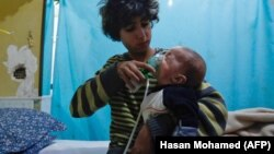 A Syrian boy holds an oxygen mask over the face of an infant after an alleged chlorine gas attack in eastern Ghouta.