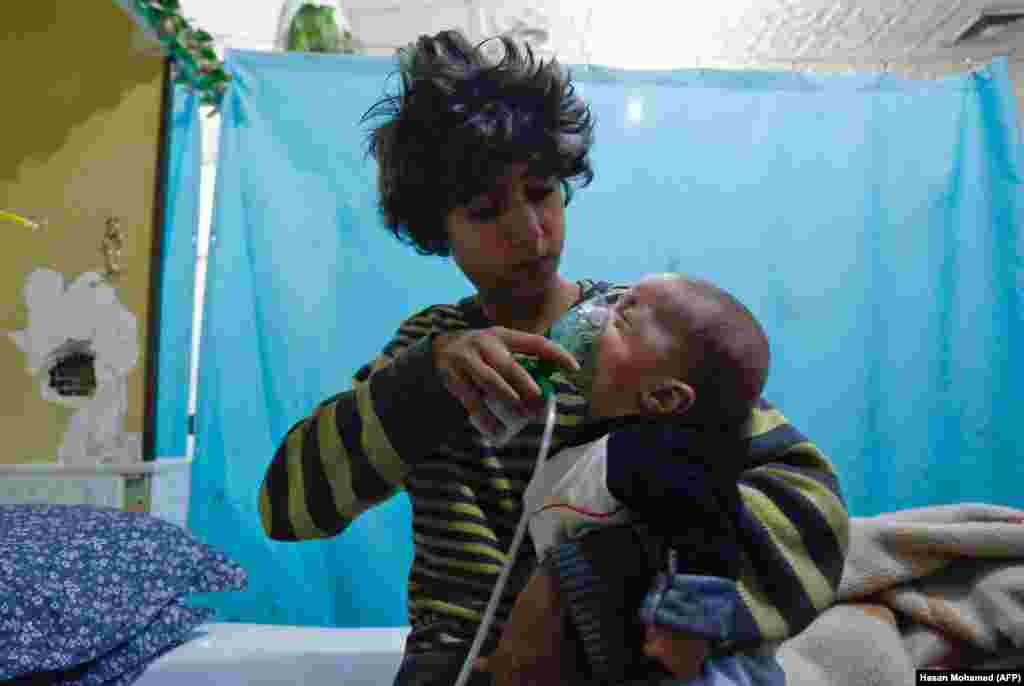 A Syrian boy holds an oxygen mask over the face of an infant at a makeshift hospital following a reported chemical gas attack on the rebel-held, besieged town of Douma in the eastern Ghouta region on the outskirts of the capital, Damascus. At least 21 cases of suffocation, including children, were reported. Since the beginning of the war in Syria in 2011, the government of Bashar al-Assad has been repeatedly accused by UN investigators of using chlorine gas or sarin gas in sometimes lethal chemical attacks. (AFP/Hasan Mohamed)