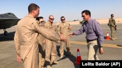 Defense Secretary Mark Esper (right) talks with U.S. troops in front of an F-22 fighter jet deployed to Prince Sultan Air Base in Saudi Arabia on October 22.