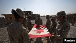 Canadian Army soldiers fold the national flag during a ceremony marking the Canadian handover of forward fire base Zangabad to U.S. forces in Kandahar Province on June 19.