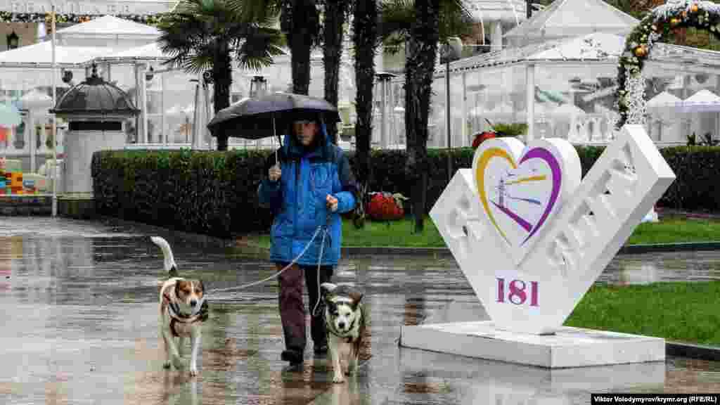 Або містян із своїми улюбленцями, що прогулюються під парасольками. Більше атмосферних фото з дощової Ялти – в нашій галереї.