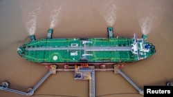 FILE PHOTO: An oil tanker unloads crude oil at a crude oil terminal in Zhoushan, Zhejiang province, China July 4, 2018. Picture taken July 4, 2018.