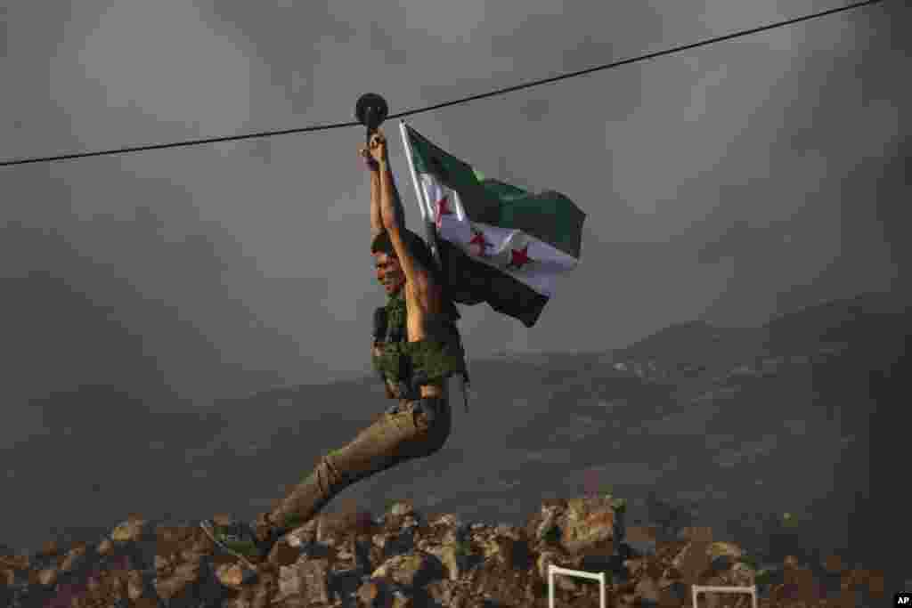 A Turkish-backed fighter from the Free Syrian Army exercises with his group's flag during military training in preparation for an anticipated Turkish incursion targeting Syrian Kurdish fighters, near Azaz in north Syria. (AP)