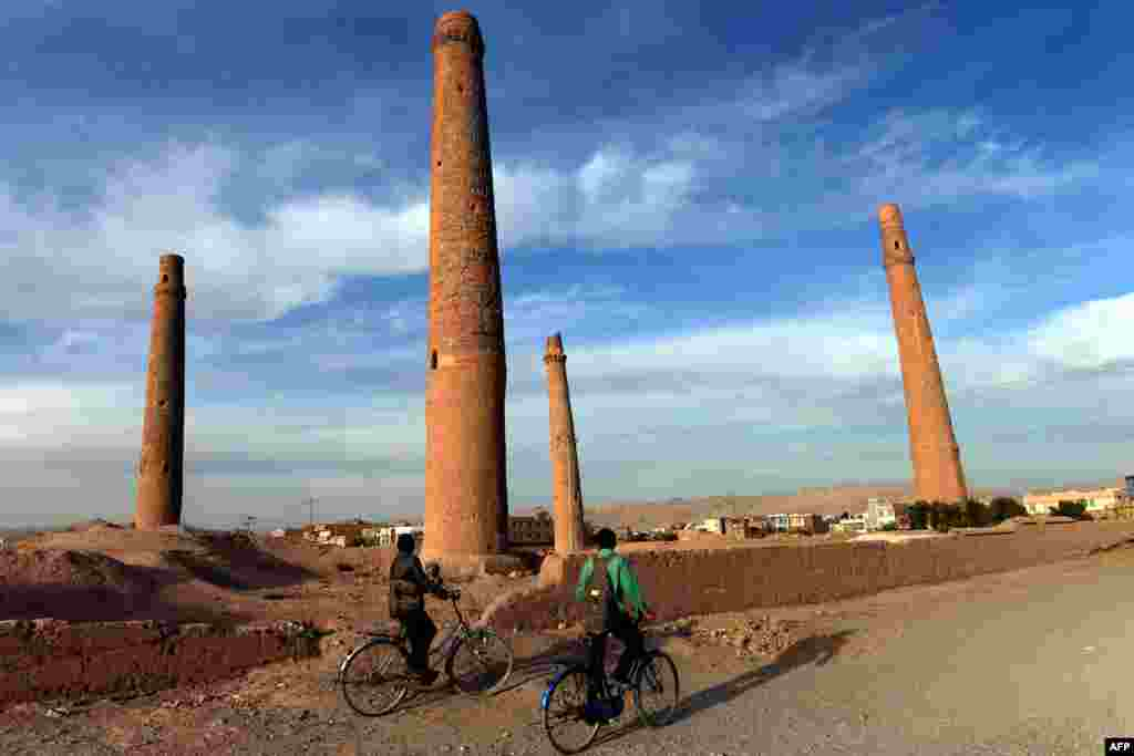 Afghan youths ride their bicycles past the historic minarets in Herat. (AFP/Aref Karimi)