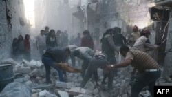 Syria - Syrian Civil Defence workers and pedestrians clear debris after an alleged air strike by Syrian government forces in the Bab al-Nairab neighboured the northern Syrian city of Aleppo on November 12, 2014