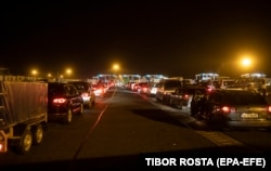Romanian and Bulgarian cars line up to cross the border between Hungary and Romania at the border station of Nagylak, Hungary, on the morning of March 18.