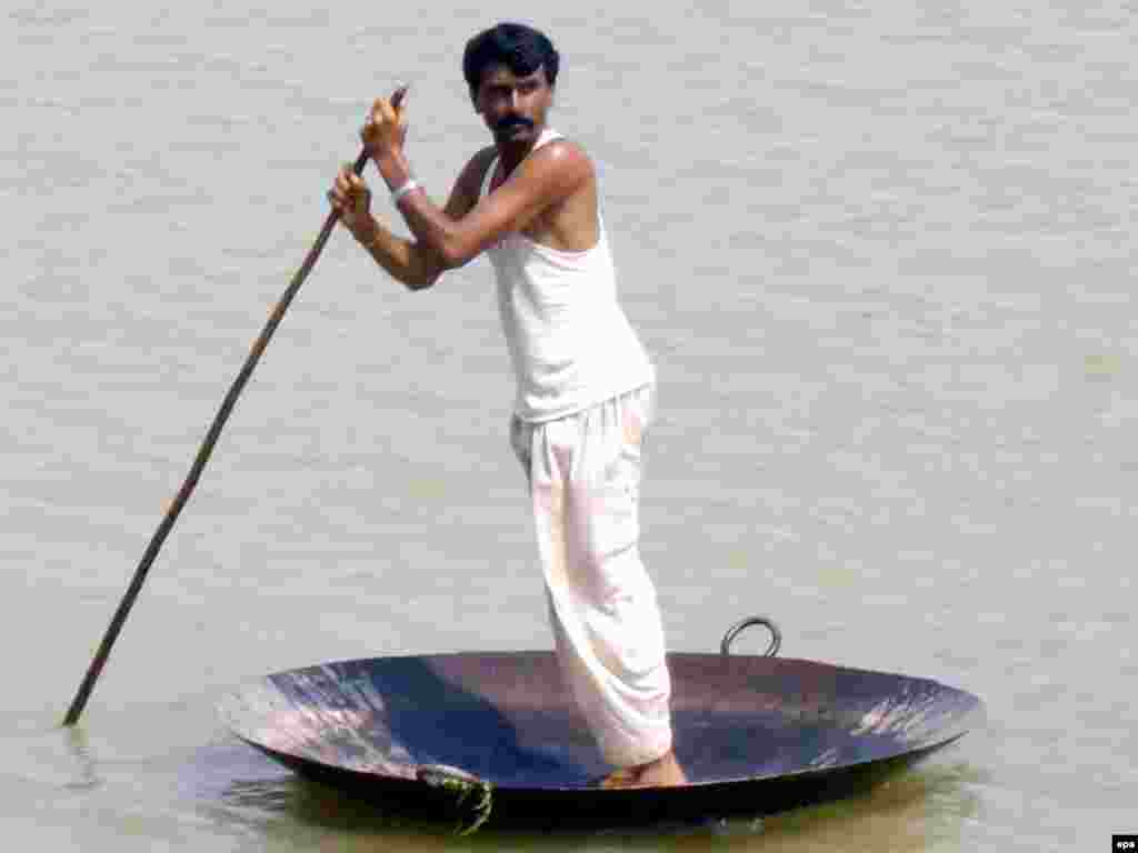 A flood victim uses an iron plate as he flees the flooded areas in Muzaffargarh in southern Punjab Province on August 11. The floods washed away millions of hectares of crops, submerged villages, and destroyed roads and bridges in the northwestern province of Khyber Pakhtunkhwa, parts of the Pakistan-administered Kashmir region, and the eastern province of Punjab. Photo by M.K. Chaudhry for epa