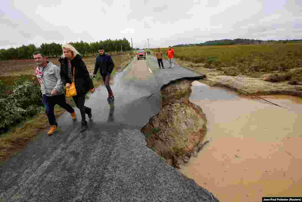 People walk on a road that was partially washed away after flash floods hit the southwestern Aude district of France. Several months' worth of rain fell in just a few hours. (Reuters/Jean-Paul Pelissier)