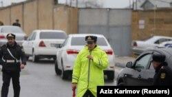 Озарбайжон полициячиси ёнғин бўлган ҳудудга олиб борувчи йўлни назорат қилмоқда.