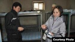 Шымкенттегі тергеу изоляторында отырған мигрантқа ақпараттық материалдар тапсырып тұрған жергілікті волонтер. (Көрнекі сурет)