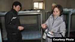 Местный волонтер раздает информационные материалы мигрантам, содержащимся в следственном изоляторе Шымкента. Иллюстративное фото.