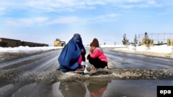 A burqa-clad woman and a girl beg on the outskirts of Kabul. (file photo)