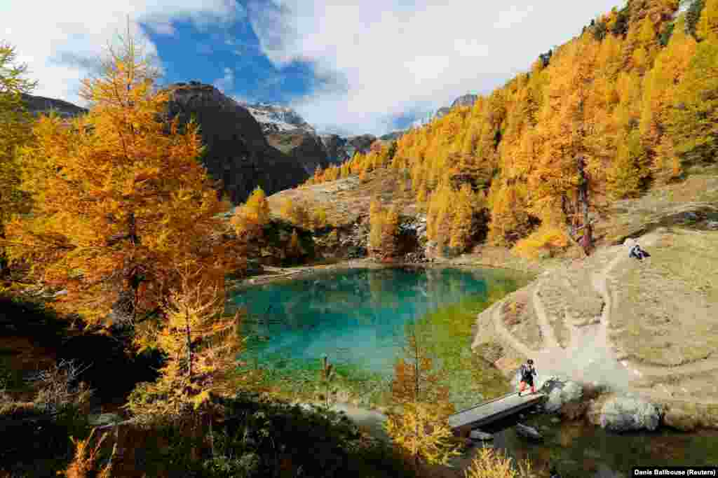 Hikers enjoy a warm autumn day at Lac Bleu near Arolla in the Val d'Herens, Switzerland. (Reuters/Denis Balibouse)