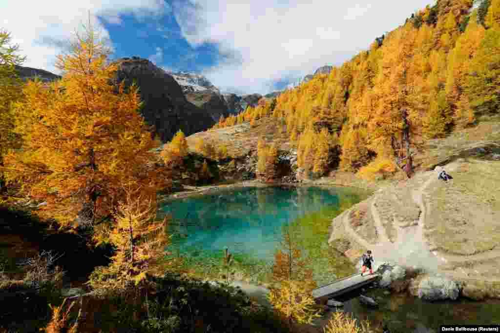 Alpinistët shijojnë një ditë të ngrohtë vjeshte në Lac Bleu pranë Arolla në Val d'Herens, Zvicër.