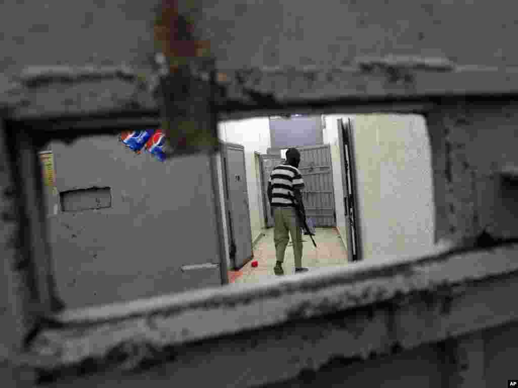A Libyan rebel fighter walks inside the Abu Salim prison in Tripoli on August 26. Photo by Sergey Ponomarev for AP