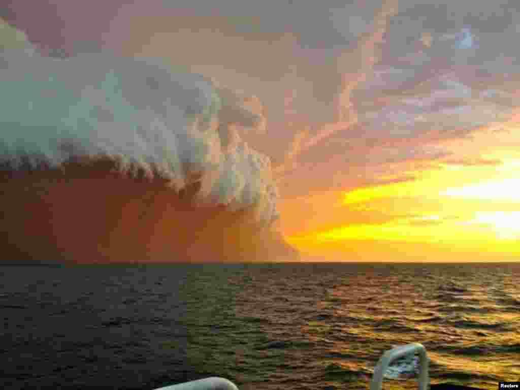 Furtună de nisip roșu cu coroană de nori călătorind în Oceanul Indian.