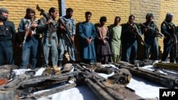 Afghan policemen stand with Taliban fighters behind a table with their seized weapons on September 29.