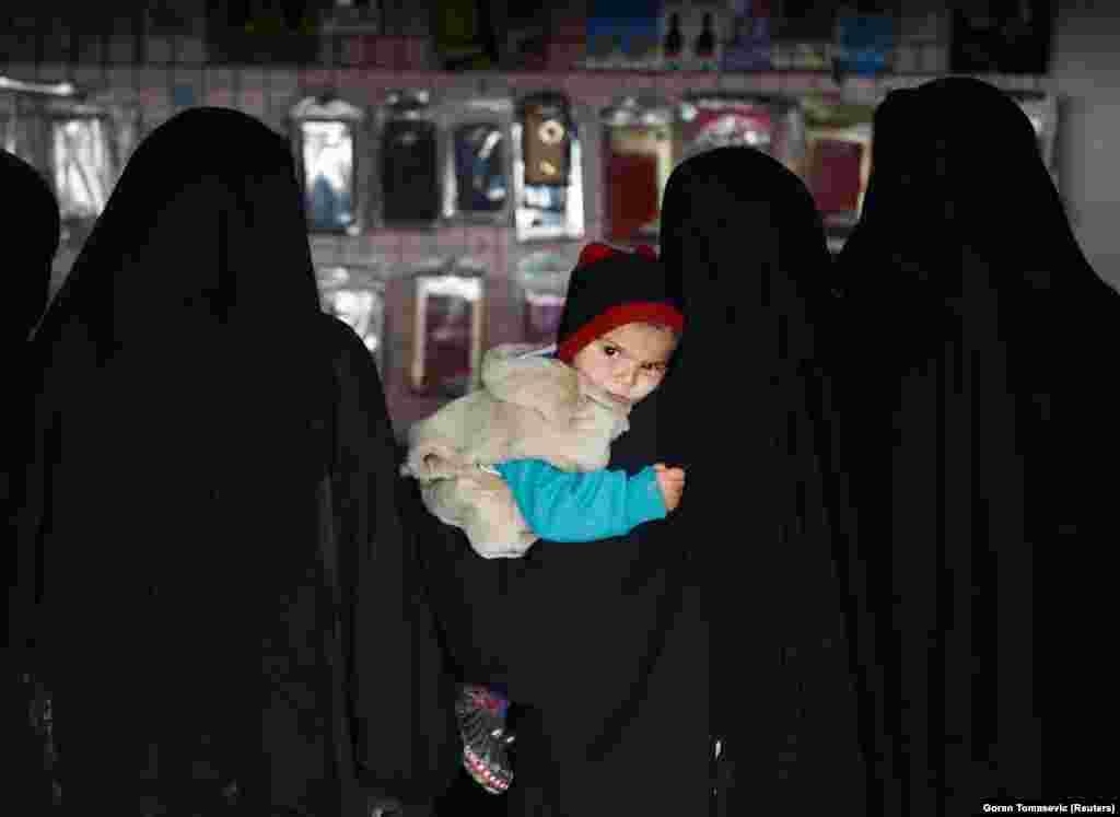 Женщина с ребенком на руках в магазине на территории лагеря аль-Холь.