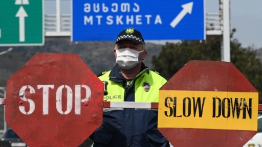 A Georgian policeman stands guard at a checkpoint in Tbilisi on April 1. They say numbers never lie. But as governments tabulate figures for COVID-19 infections and deaths, experts say the data is likely incomplete.