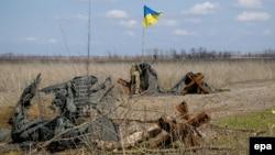 Украинский военнослужащий устанавливает национальный флаг возле позиции вблизи села Водяное Донецкой области, 22 марта 2017 года