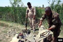 Ирак әскерилері ИМ жазалаған Ирак жауынгерлерінің мәйіттері мен қару-жарақтарына қарап тұр. Тикрит, 8 сәуір 2015 жыл.