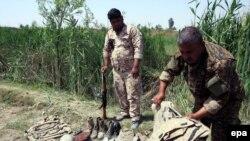 Иракские военнослужащие осматривают человеческие останки и военное снаряжение на месте массового захоронения иракских солдат, убитых боевиками группировки «Исламское государство». Тикрит, 8 апреля 2015 года.