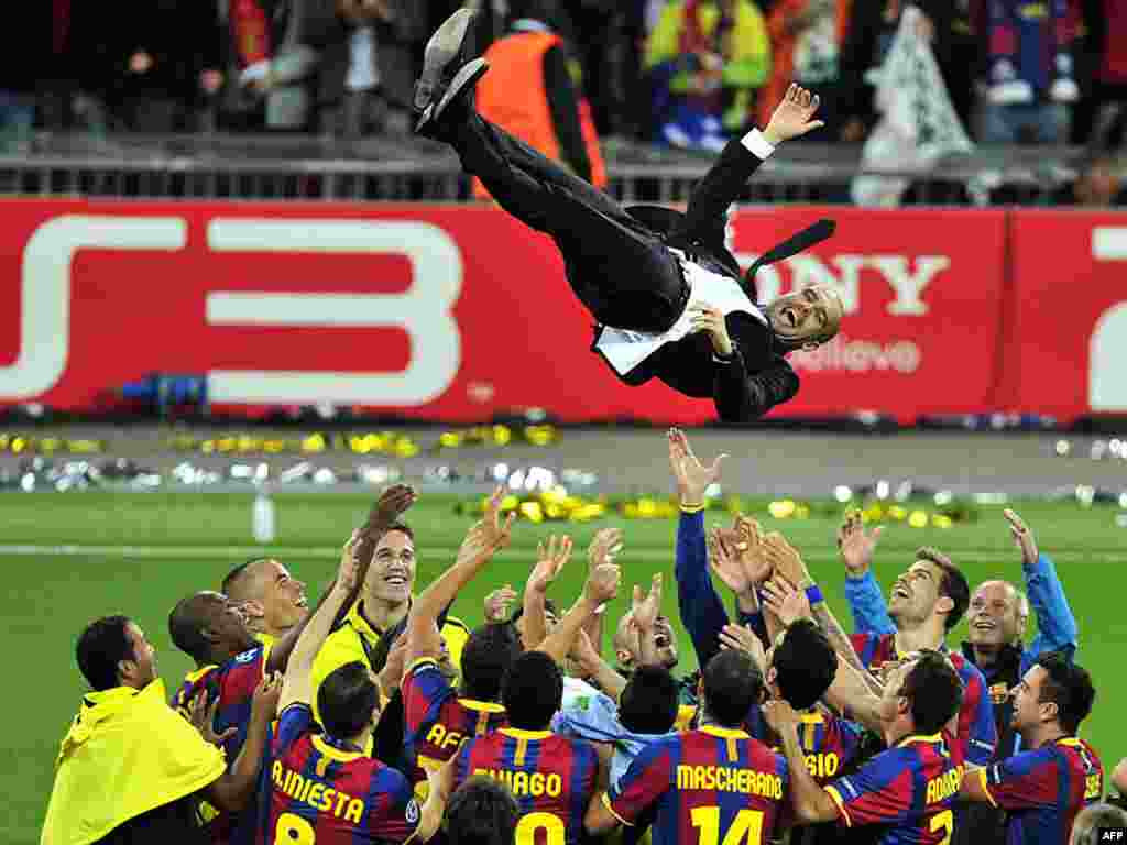 Barcelona soccer coach Pep Guardiola is thrown in the air after his team's Champions League victory on May 29.Photo by Glyn Kirk for AFP