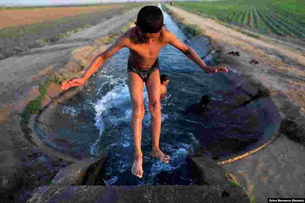 A boy cools off in an irrigation canal on the outskirts of Raqqa, Syria. (Reuters/Zohra Bensemra)
