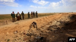 Iraq -- Members of the Yazidi minority search for clues that might lead them to missing relatives in the remains of people killed by the IS jihadist group, a day after Kurdish forces discovered a mass grave near the Iraqi village of Sinuni, 3Feb2015.