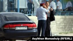 """""""Жаңаөзен сотының"""" алдында көлікті тоқтатып тұрған тұрған жол полициясы қызметкері. Ақтау, 14 мамыр 2012 жыл."""