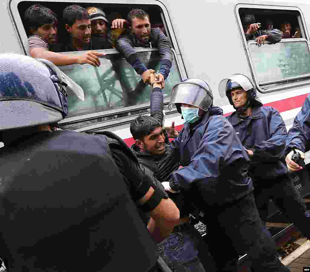 Croatian police push back a migrant who had tried to climb through the window to get aboard a train bound for Hungary and Austria at a railway station at the Croatian-Serbian border, near Tovarnik, Croatia. (epa/Antonio Bat)