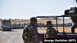 Представители сирийских правительственных сил наблюдают за эвакуацией беженцев, август 2017 год