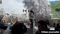 تصویری در شبکه های اجتماعی منتشر شد که براساس آن، دختری در نزدیکی خیابان انقلاب تهران روسری خود را به یک چوب وصل کرده و بر روی یکی از پستهای انتقال برق ایستاده است
