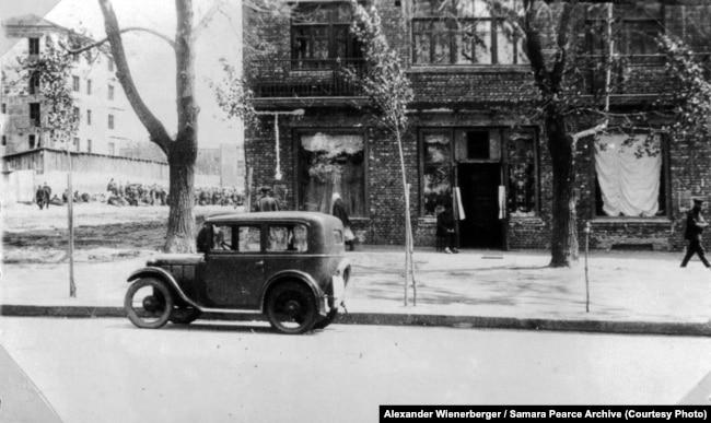 «Крамниця для іноземців і наш автомобіль BMW перед ним» (авторський підпис). Харків, 1933 рік. На фото особистий автомобіль Александра Вінербергера, який він придбав й привіз із Австрії. Найімовірніше, авто припарковане біля крамниці Всеукраїнської торгової мережі постачання чужоземцям у промисловому районі Харкова. Саме тут Вінербергер купував продукти та переправляв їх своїй дружині у кримський санаторій. Фото Александра Вінербергера. Публікується вперше. Надано власником авторських прав Самарою Пірс
