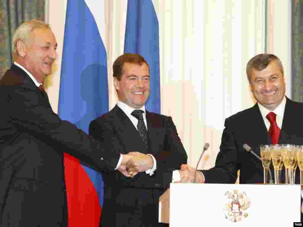 Рускиот претседател Дмитриј Медведев (во средина) се ракува со лидерите на Јужна Осетија и Абхазија, Едуард Кокоити (десно) и Сергеј Багапш во Москва во септември 2008 година. На 26.08.2008 година Русија ги призна двата региона како независни држави. Москва држеше трупи во двата региона, што само неколку други земји, вклучително и Сирија, ги признаа во 2018 година како независни.