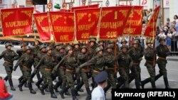 Военнослужащие в красноармейской форме образца 1943-1945 годов с копиями знамен советских фронтов завершающего этапа Второй мировой войны маршируют по центральной улице Симферополя, 24 июня 2020 года