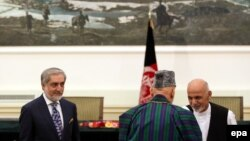 Presidential candidates Abdullah Abdullah (left) and Ashraf Ghani talk with outgoing President Hamid Karzai during a September 21 ceremony to form a unity government in Kabul.