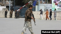 An Afghan soldier walks near the site of an explosion in Kabul in March.