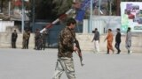 An Afghan policeman walks near the site of an explosion in Kabul on March 21
