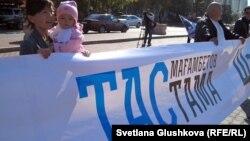"""Женщина с ребенком на руках на площади перед акиматом Астаны держит растяжку: """"Тасмағамбетов, тастама"""" (Тасмагамбетов, не выгоняй). Астана, 25 сентября 2012 года."""