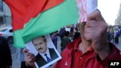 Чоловік тримає прапор Білорусі та портрет президента Білорусі Олександра Лукашенка під час опозиційного мітингу у центрі Мінська. 10 вересня 2015 року